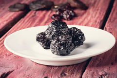 Dried plums in the plate Royalty Free Stock Photos