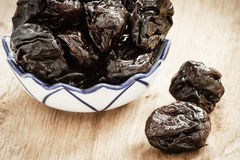 Dried plums prunes in bowl on wooden table Royalty Free Stock Photos
