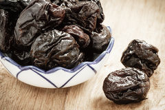 Dried plums prunes in bowl on wooden table Stock Photo