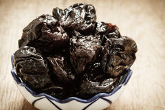Dried plums prunes in bowl on wooden table Royalty Free Stock Photo