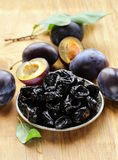 Dried plums prunes and fresh berries Stock Images