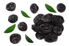 Dried plums - prunes with green leaves isolated on white background. top view royalty free stock image