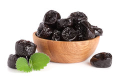 Dried plums or prunes with a mint leaf in wooden bowl isolated on white background Stock Images