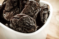 Dried plums prunes in white bowl on wooden table Stock Photos