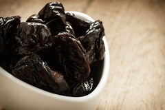 Dried plums prunes in white bowl on wooden table Stock Images