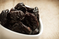 Dried plums prunes in white bowl on wooden table Royalty Free Stock Photo