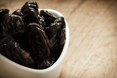 Dried plums prunes in white bowl on wooden table Royalty Free Stock Photos