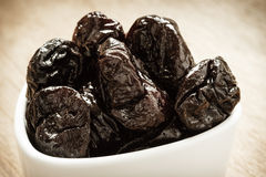 Dried plums prunes in white bowl on wooden table Royalty Free Stock Photography