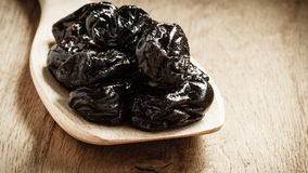Dried plums prunes on wooden spoon Stock Image