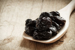 Dried plums prunes on wooden spoon Stock Photos