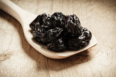 Dried plums prunes on wooden spoon Royalty Free Stock Images