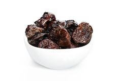 Dried plums in white bowl isolated on white background. Royalty Free Stock Photos
