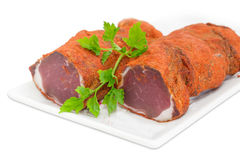 Dried pork tenderloin and parsley twig closeup on white dish Stock Image