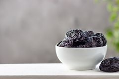 Dried prunes in a white bowl.  royalty free stock photography