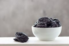 Dried prunes in a white bowl.  stock photos