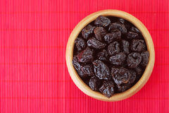 Dried prunes in wooden bowl Royalty Free Stock Photos