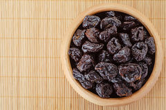 Dried prunes in wooden bowl Stock Photos