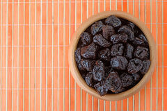 Dried prunes in wooden bowl Stock Image