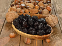 Dried prunes in a wooden bowl Royalty Free Stock Photos