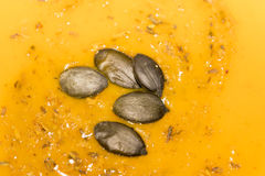 Dried pumpkin pips on pumpkin soup. Dried pumpkin pips and scattered spices on pumpkin soup in a close up full frame background view Stock Photos