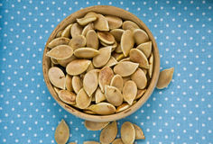 Dried pumpkin seeds in a brown artisan bowl spred on a blue napk Stock Photos