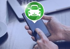 Hand holding phone with car icon at desk Stock Images