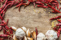 Dried red chili pepper and fresh garlic isolated on wooden backg Royalty Free Stock Photography