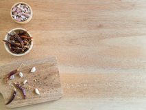 Dried red chili peppers and garlic on wooden board Stock Image