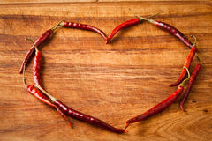 Dried red chili peppers  in heart shape on rustic, dark wood cut Stock Photo