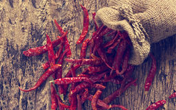 Dried red chili peppers in sack with on old wooden background,Vintage color tone Stock Photography