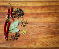 Dried red chili peppers and spices on rustic, dark wood cutting Stock Photo