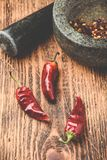 Dried red chili peppers on wooden surface with mortar and pestle. Sun dried red chili peppers on wooden surface with mortar and pestle royalty free stock images