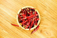 Dried red chili in a wooden bowl. Stock Photos
