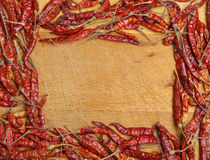 Dried Red Chilli Frame. Dried red chillies forming a frame around a wooden chopping board Stock Photo