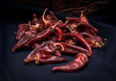 Dried red hot chili peppers are lying in a heap, glitering with different shades of red Stock Image