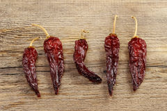 Dried red hot chili peppers on wooden background Royalty Free Stock Photos