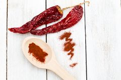 Dried red hot chili peppers on a wooden white background. Flat l Stock Images