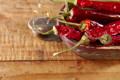Dried red hot chillies pepper in old wooden bowl Royalty Free Stock Photo