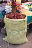 Dried red peppers in large sack on the market. stock image