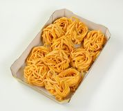 Dried ribbon pasta. Box of dried ribbon pasta bundles on white background royalty free stock photography