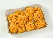 Dried ribbon pasta. Box of dried ribbon pasta bundles on white background royalty free stock images