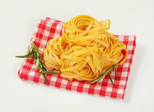 Dried ribbon pasta. Bundles of dried ribbon pasta on checkered place mat royalty free stock photo