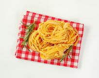 Dried ribbon pasta. Bundles of dried ribbon pasta on checkered place mat stock images