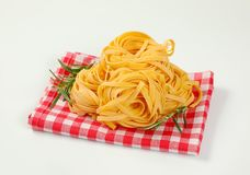 Dried ribbon pasta. Bundles of dried ribbon pasta on checkered place mat stock photo