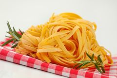 Dried ribbon pasta. Bundles of dried ribbon pasta on checkered place mat- close up stock photo