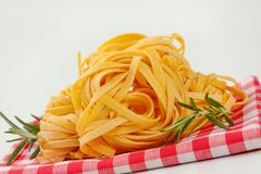 Dried ribbon pasta. Bundles of dried ribbon pasta on checkered place mat - close up stock photos