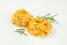 Dried ribbon pasta. Bundles of dried ribbon pasta on white background stock photography