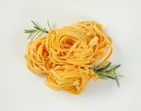 Dried ribbon pasta. Bundles of dried ribbon pasta on white background stock image