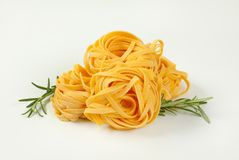 Dried ribbon pasta. Bundles of dried ribbon pasta on white background royalty free stock photo