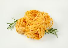Dried ribbon pasta. Bundles of dried ribbon pasta on white background royalty free stock photography